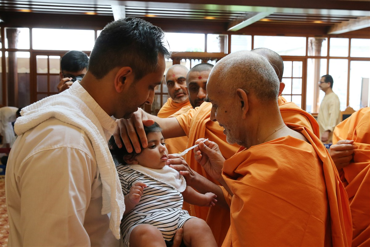 Swamishri performs annaprashan samskar to a young child