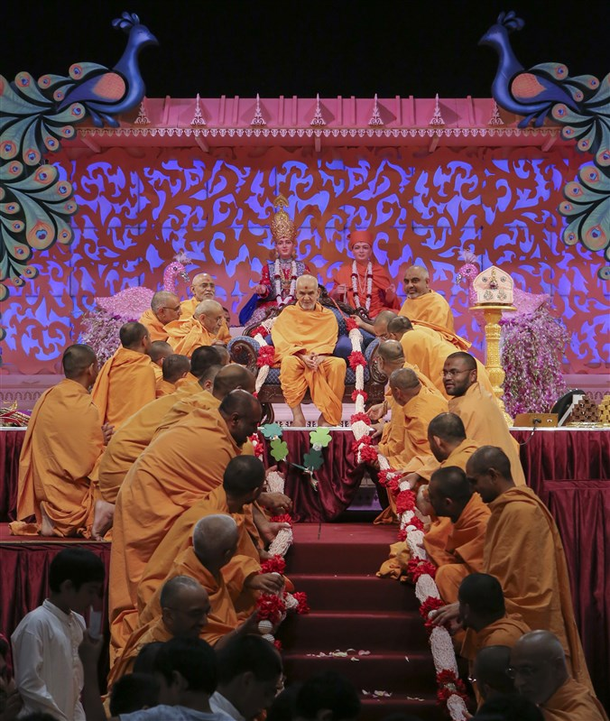 Sadhus honour Swamishri with a garland composed of rice puffs embellished with the 'Swaminarayan' mahamantra