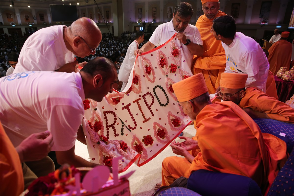 Representative volunteers offer Swamishri a decorative shawl