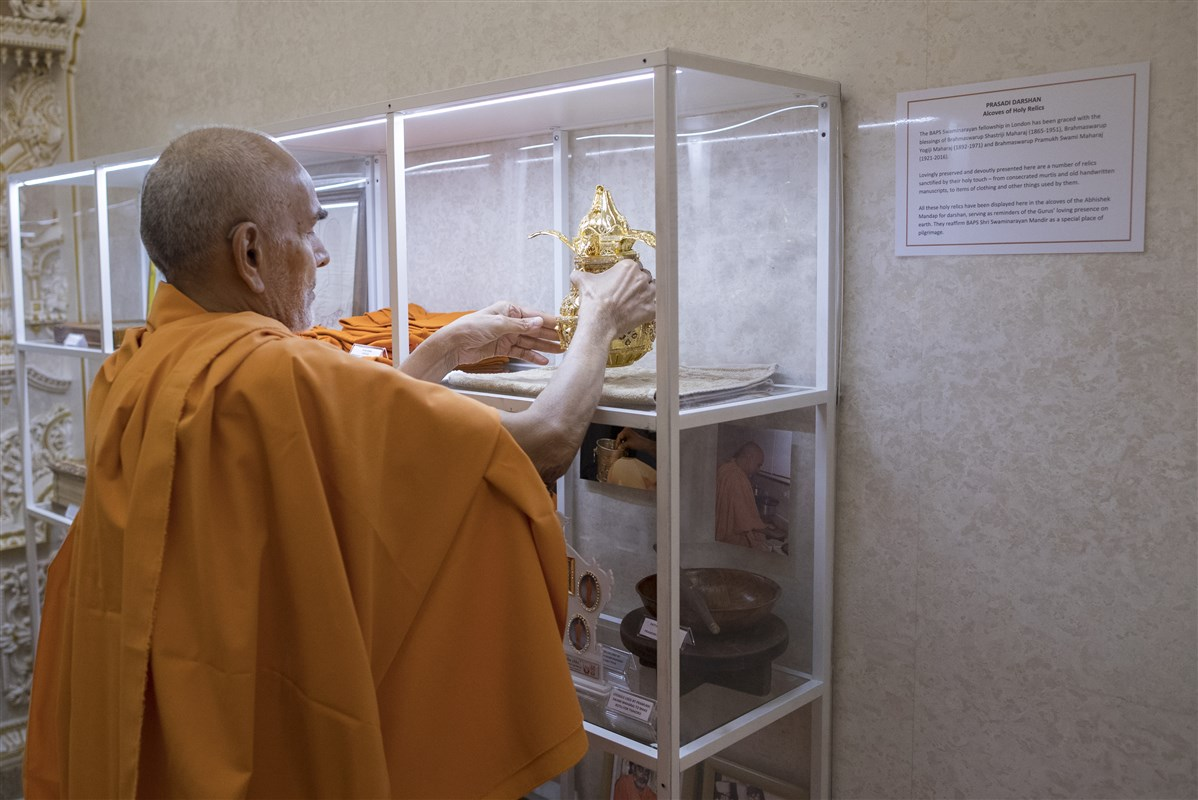 Swamishri places a sanctified kalash with Pramukh Swami Maharaj's holy ashes in the prasadi display alongside other holy relics of the Guru Parampara