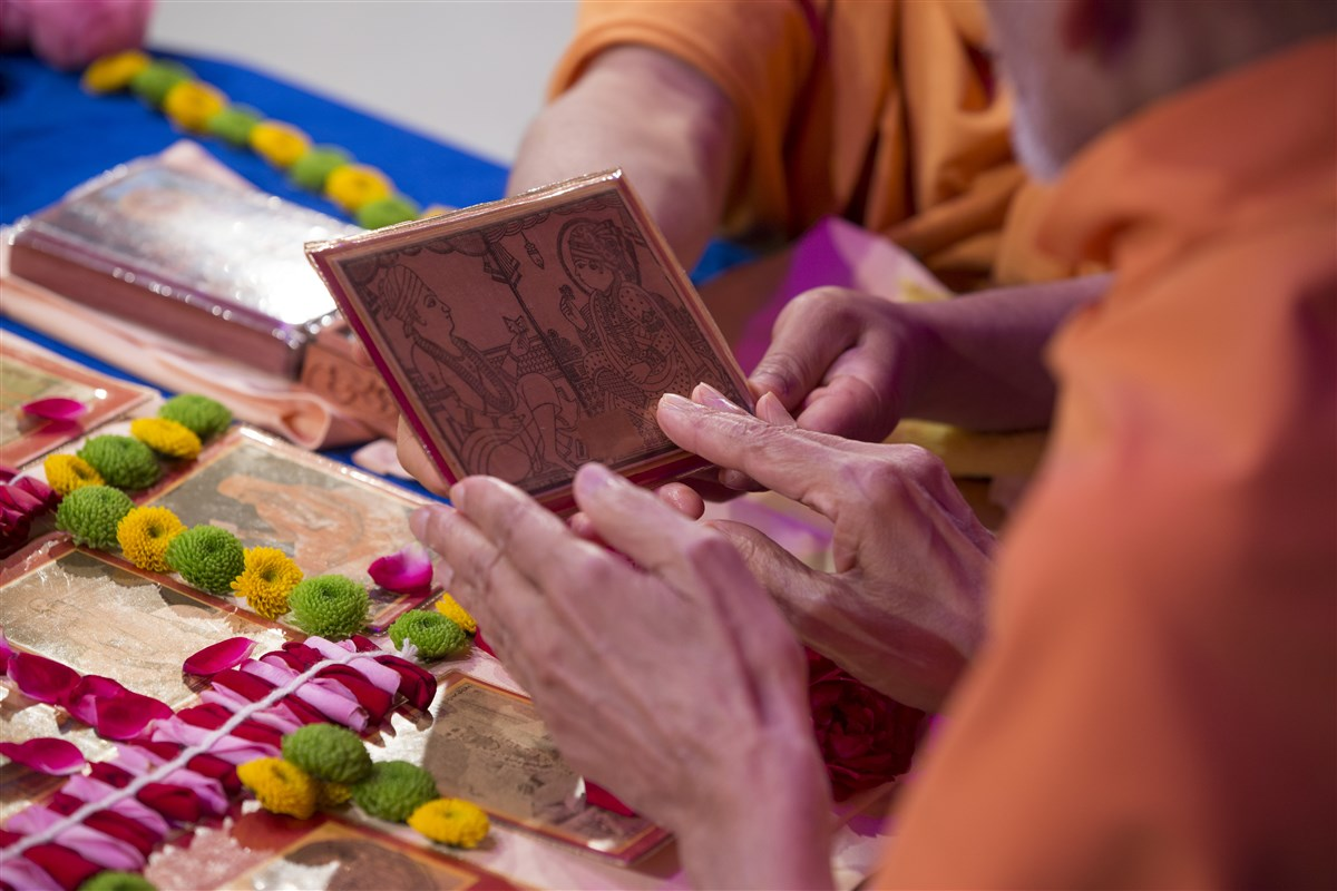 Swamishri reverentially touches the murtis in his puja