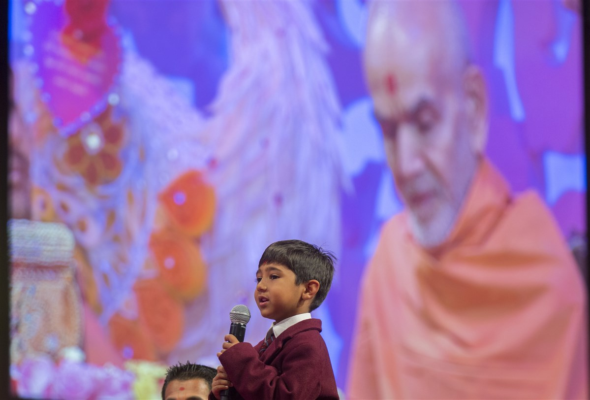 A young pupil from The Swaminarayan School presents in Swamishri's puja