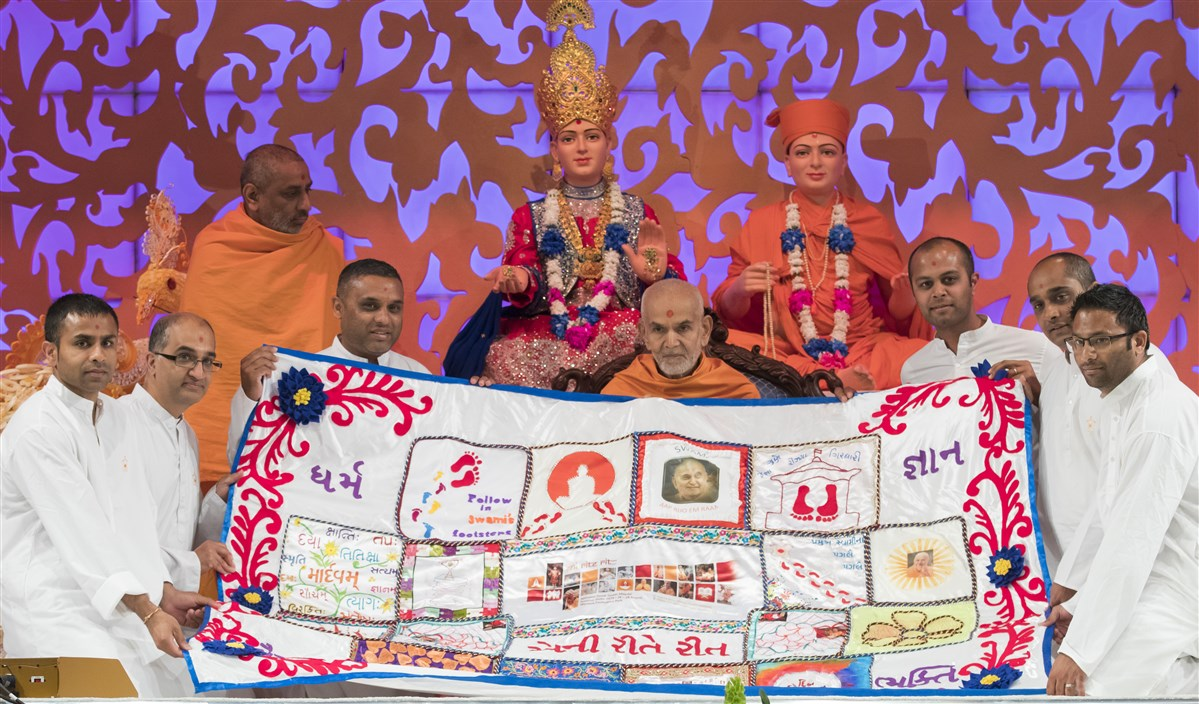 Lead Yuvak Mandal volunteers offer a decorative shawl to Swamishri