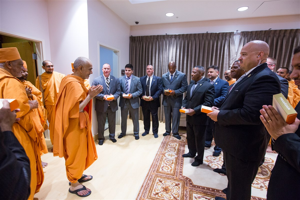 Swamishri meets with the Gwinnett County Sheriff's Department officers who provided escort from the airport