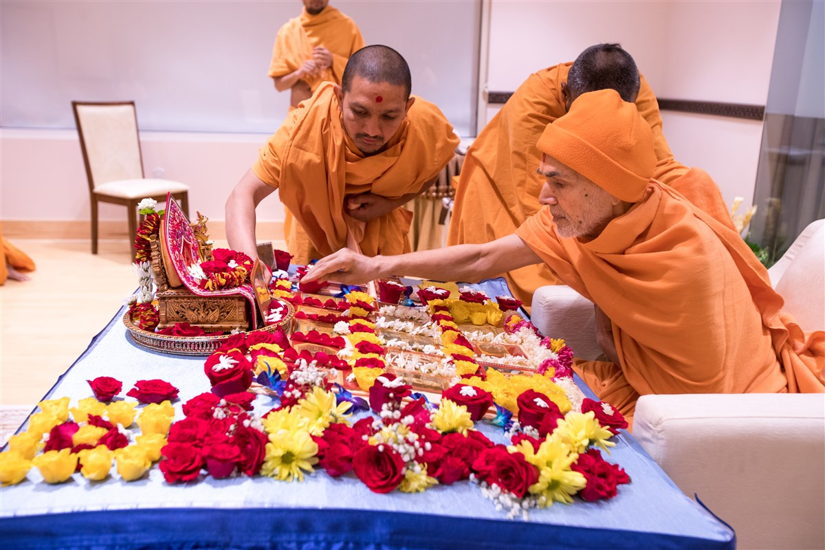 Swamishri arranges flowers surrounding the murtis in his puja