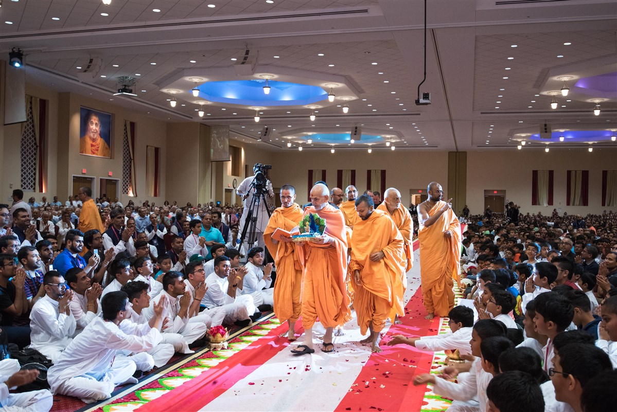 Youths offer flowers at Swamishri's feet as he arrives in the welcome assembly