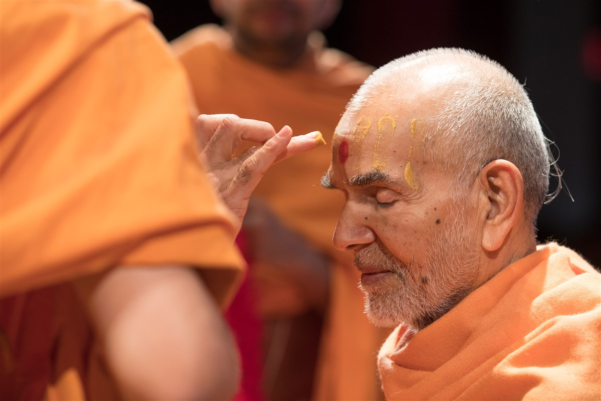 Swamis apply sandalwood to Swamishri's forehead as a welcoming gesture