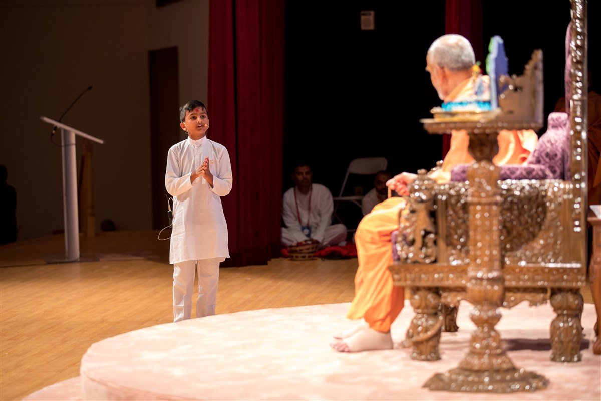 A child interacts with Swamishri to welcome him to North America