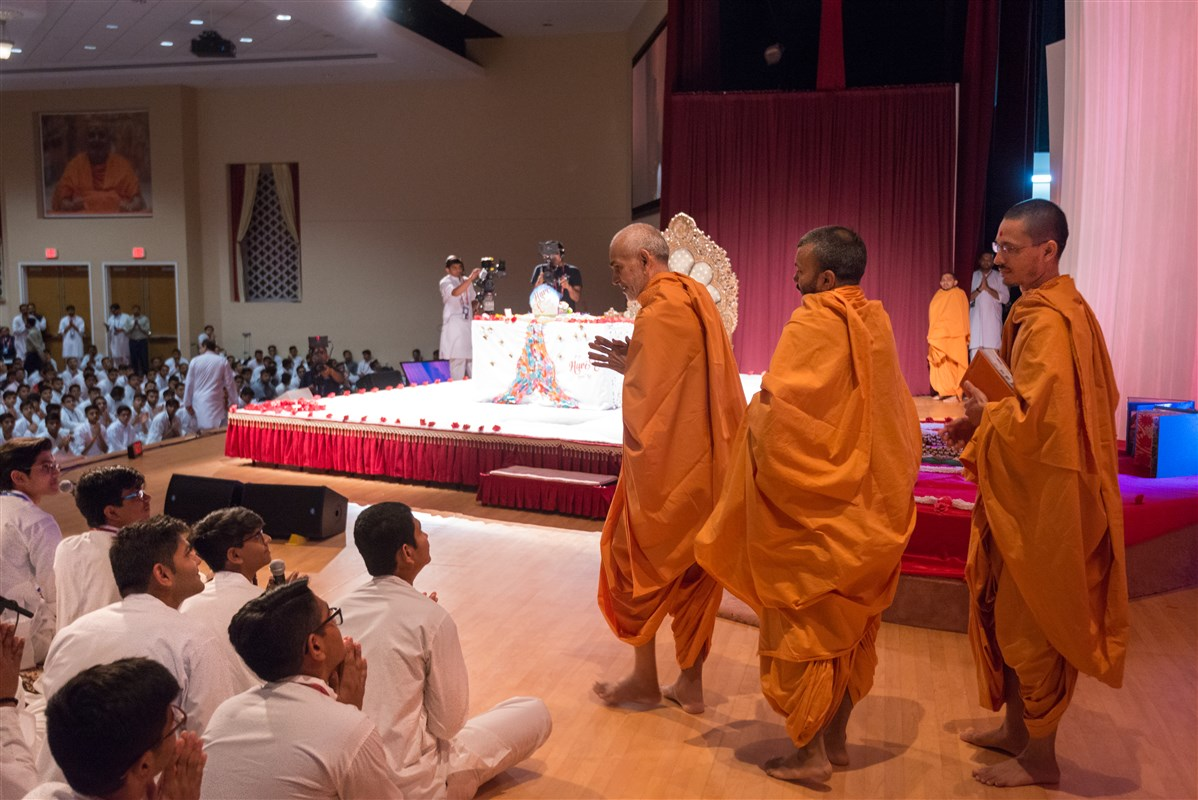 Swamishri folds his hands to youths singing in puja