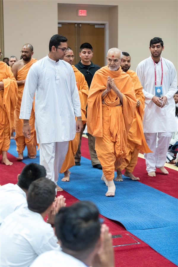 Swamishri enters the Kishore-Kishori Din program with his hands folded