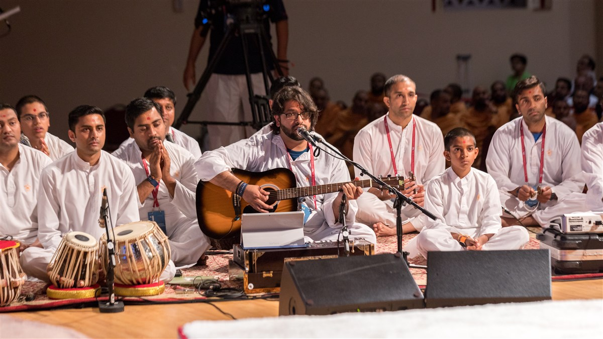 Youths sing kirtans during Swamishri's puja