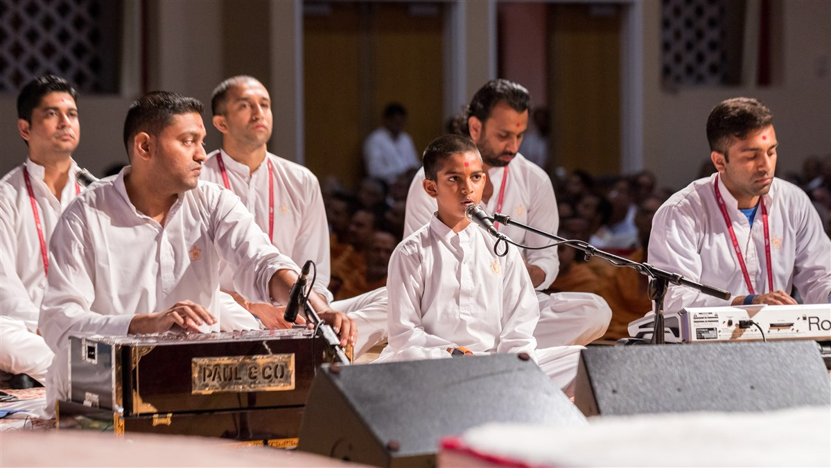 Youths sings kirtan during Swamishri's puja