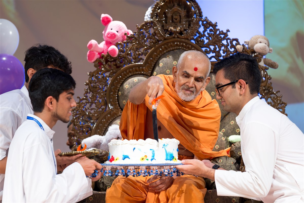 Swamishri cuts a cake for the children