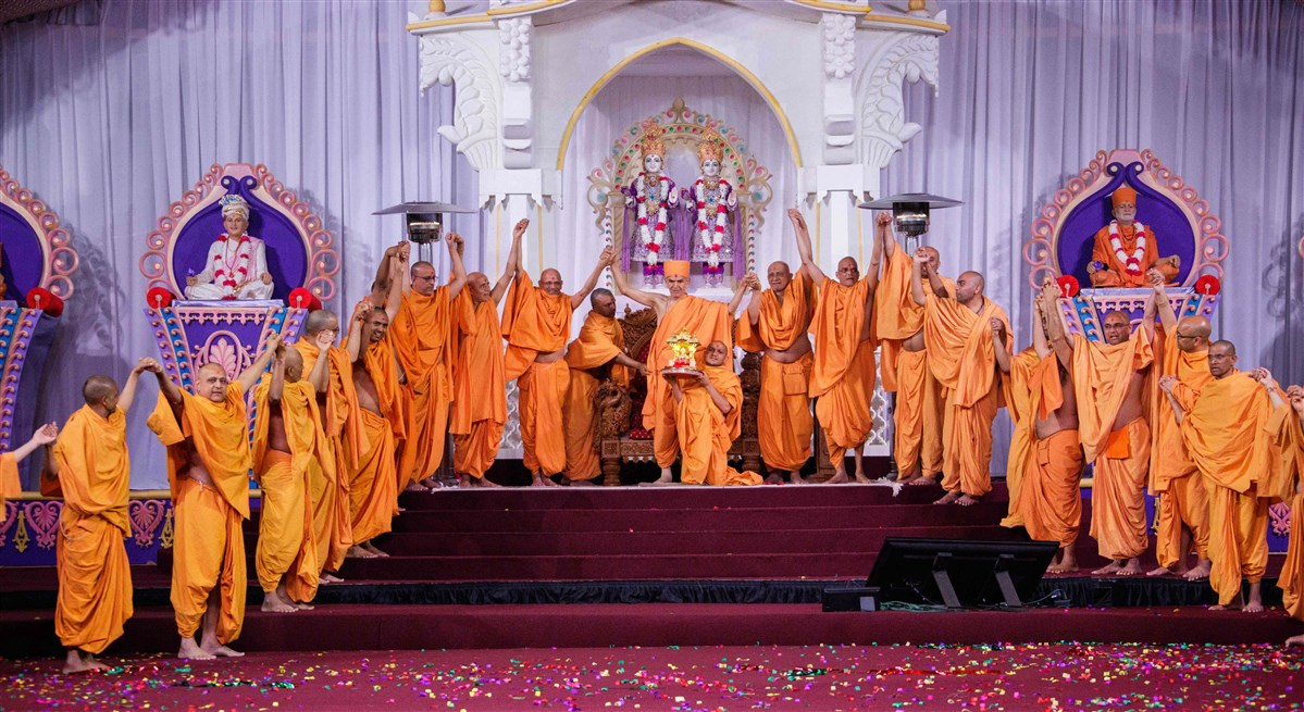 Swamis join hands with Swamishri in a gesture of unity