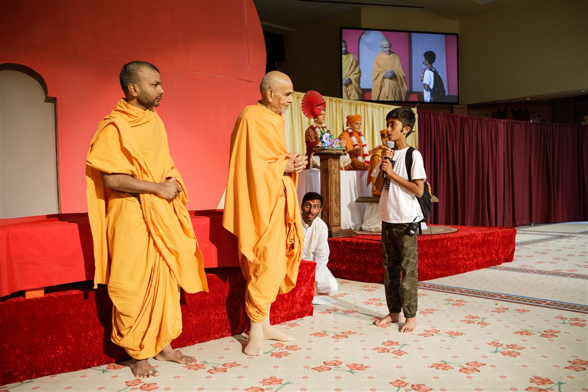 A child interacts with Swamishri during the Bal-Balika Din