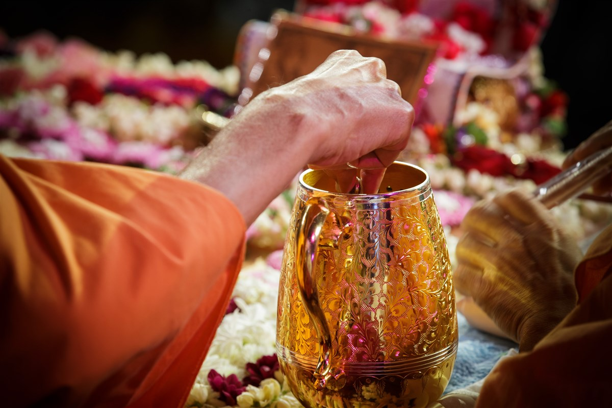 Swamishri sanctifies water with holy relics of Bhagwan Swaminarayan and the Guru Parampara