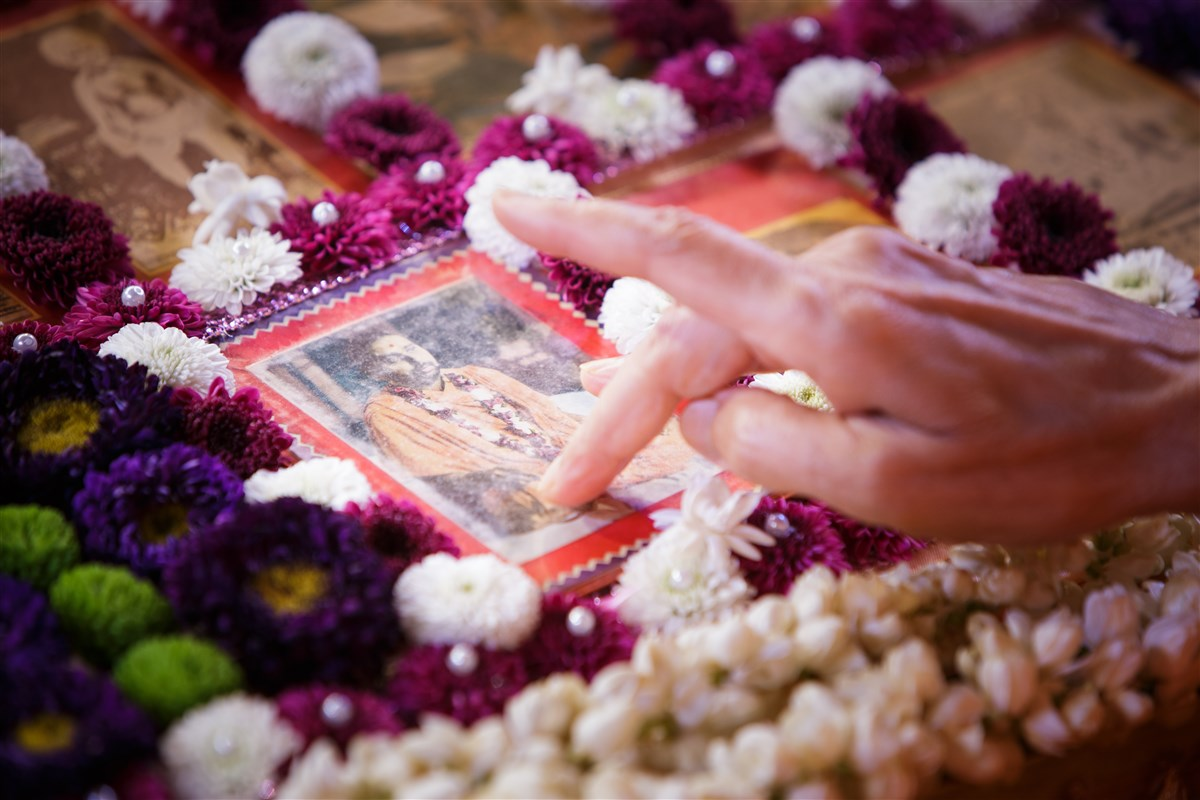 Swamishri touches the feet of the murti of Pramukh Swami Maharaj