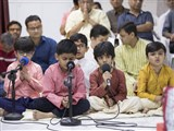 Children sing kirtans in the assembly