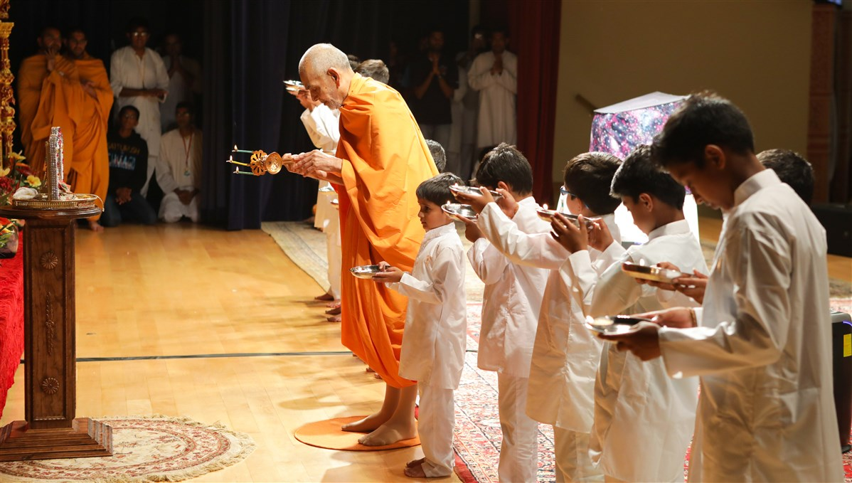 Swamishri performs the evening arti with children, 18 July 2017