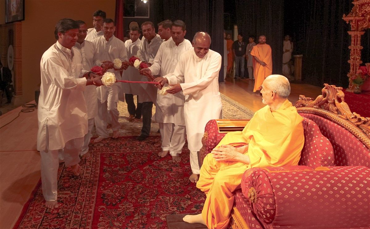 Devotees offer a garland to Swamishri, 18 July 2017
