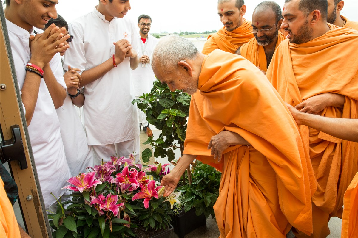 Swamishri appreciates plants offered by a devotee