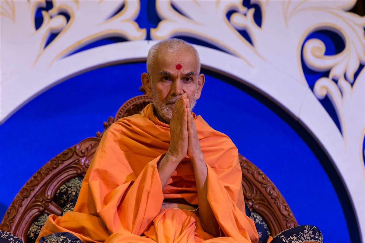 Swamishri folds his hands to the devotees in the audience