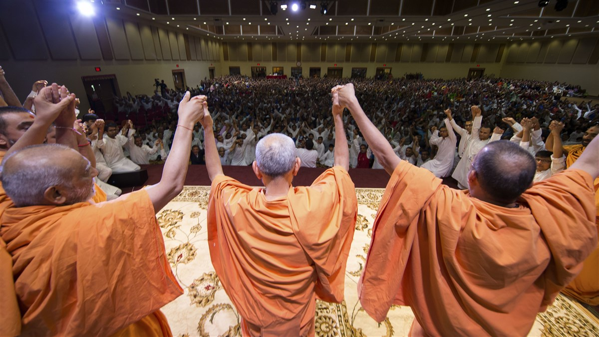 Mahant Swami Maharaj joins hands with swamis and devotees in a gesture of unity