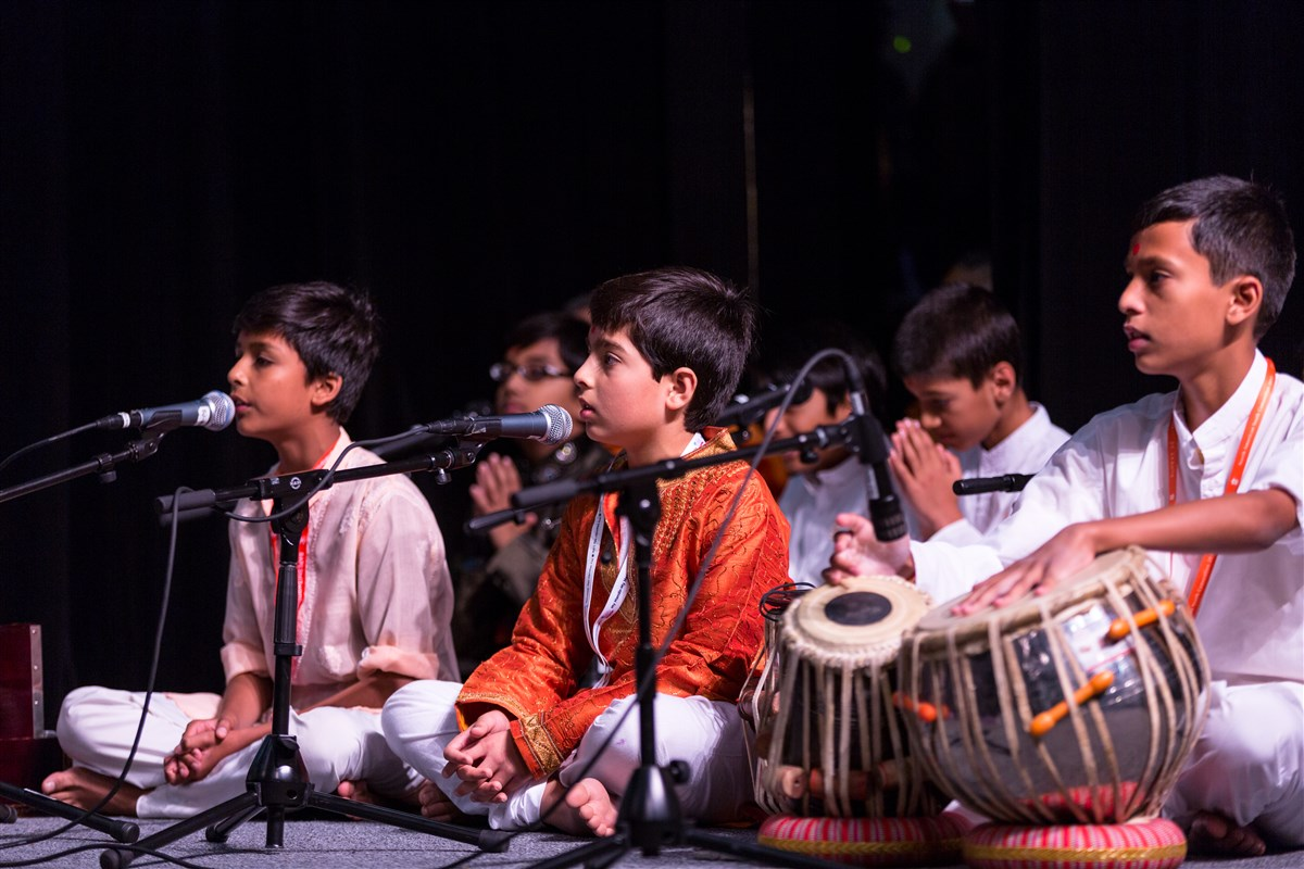 Children sing kirtans before Swamishri during his puja