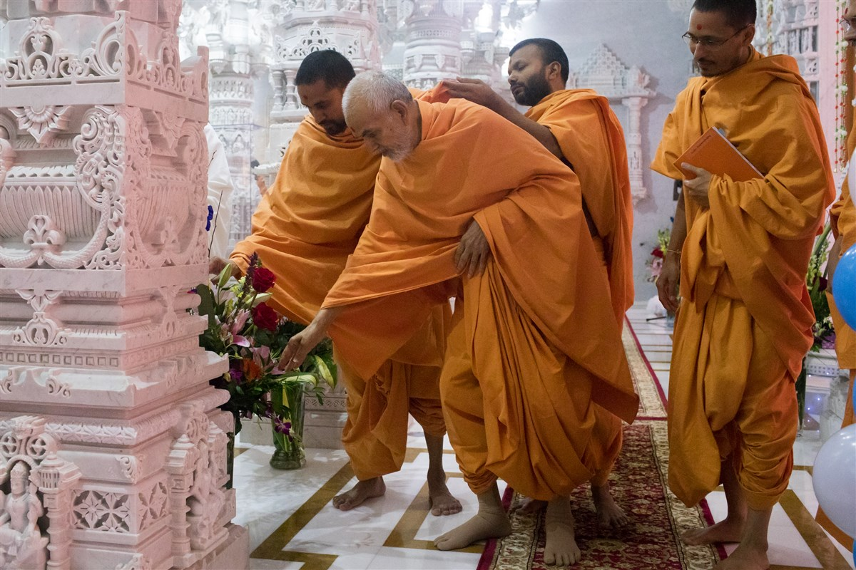 Swamishri appreciates a  bouquet of flowers offered by a devotee