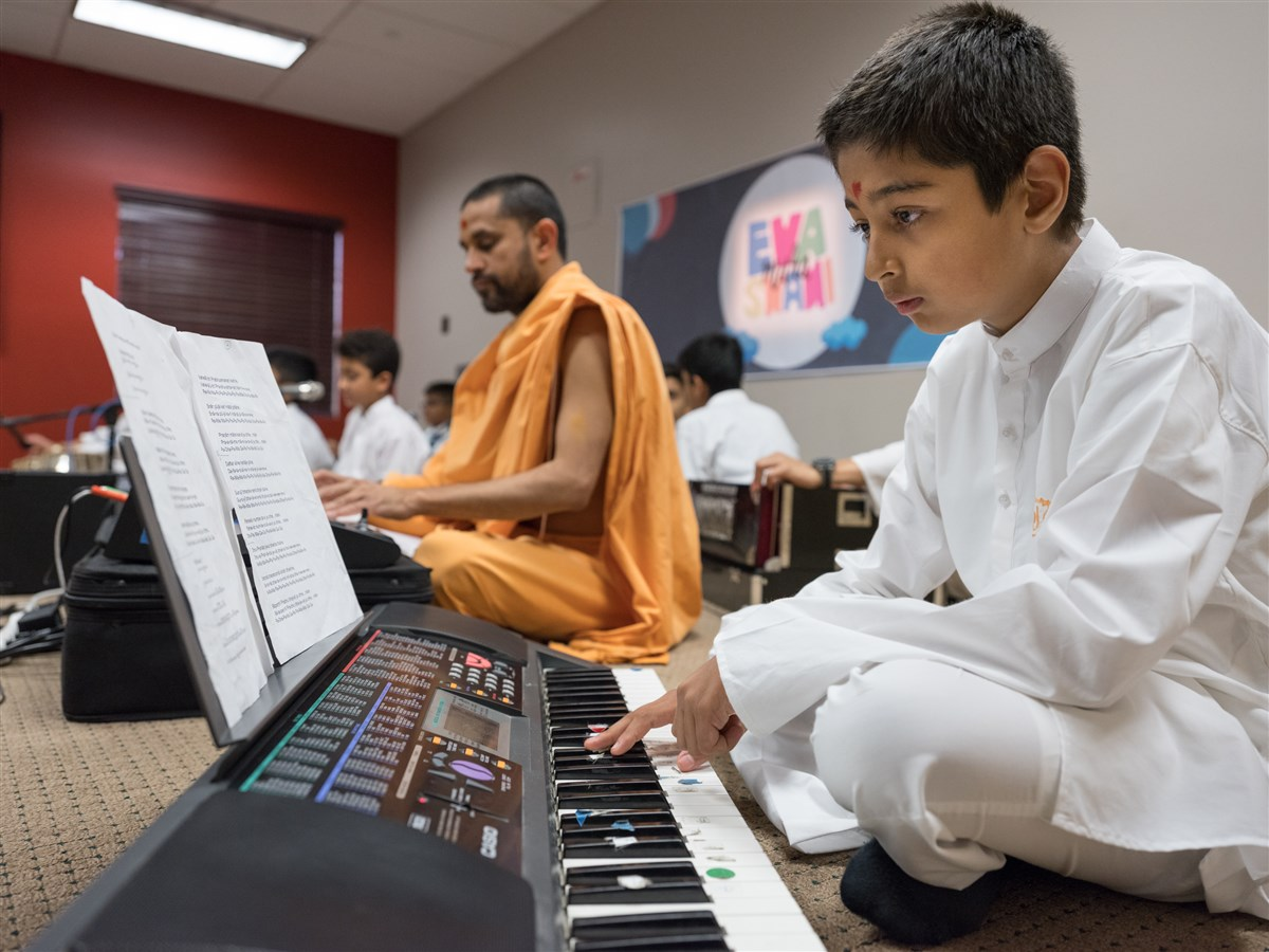 A child plays the keyboard in Swamishri's puja