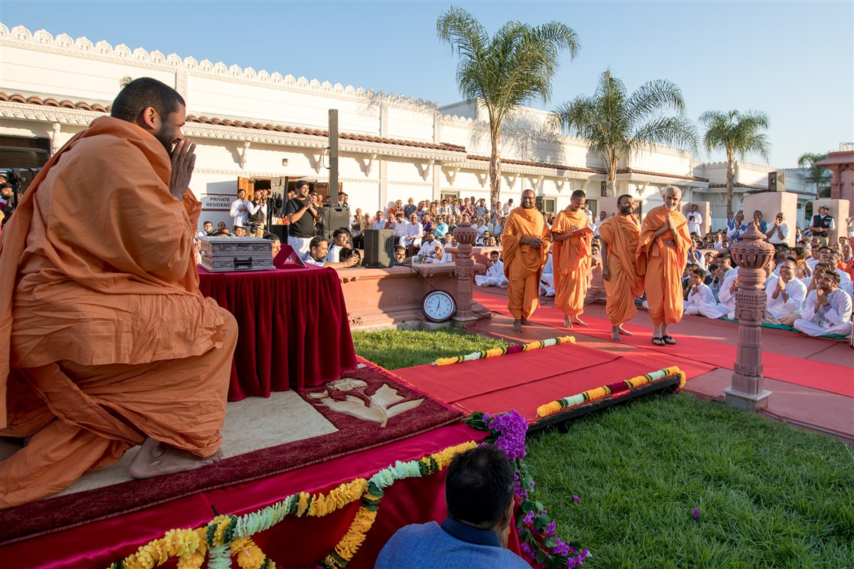 Param Pujya Mahant Swami Maharaj greets Swamis and devotees with folded hands