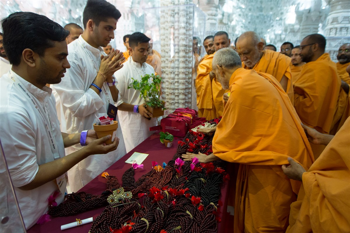 Swamishri sanctifies malas to be given out during the Yuvak-Yuvati Din