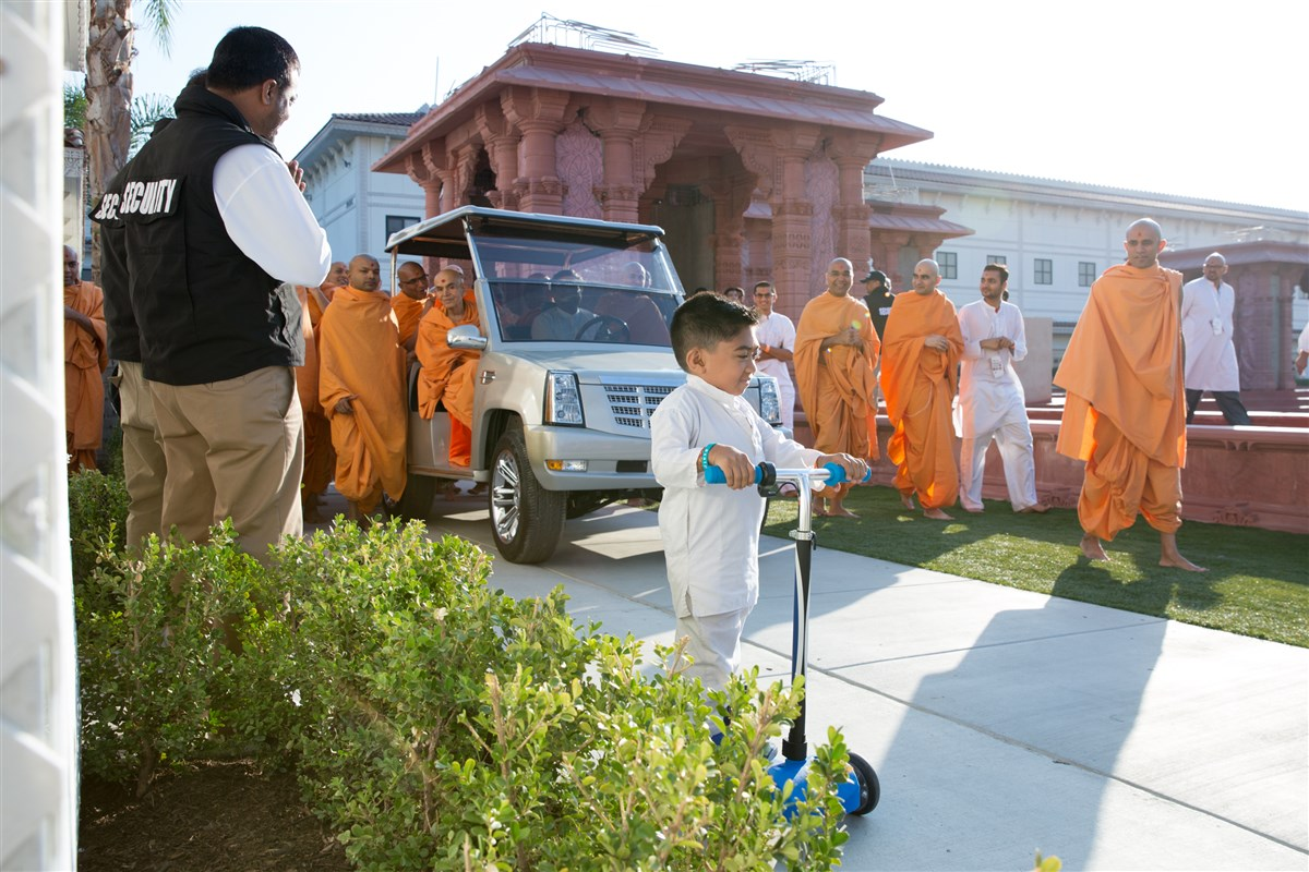 A child leads Swamishri towards the mandir