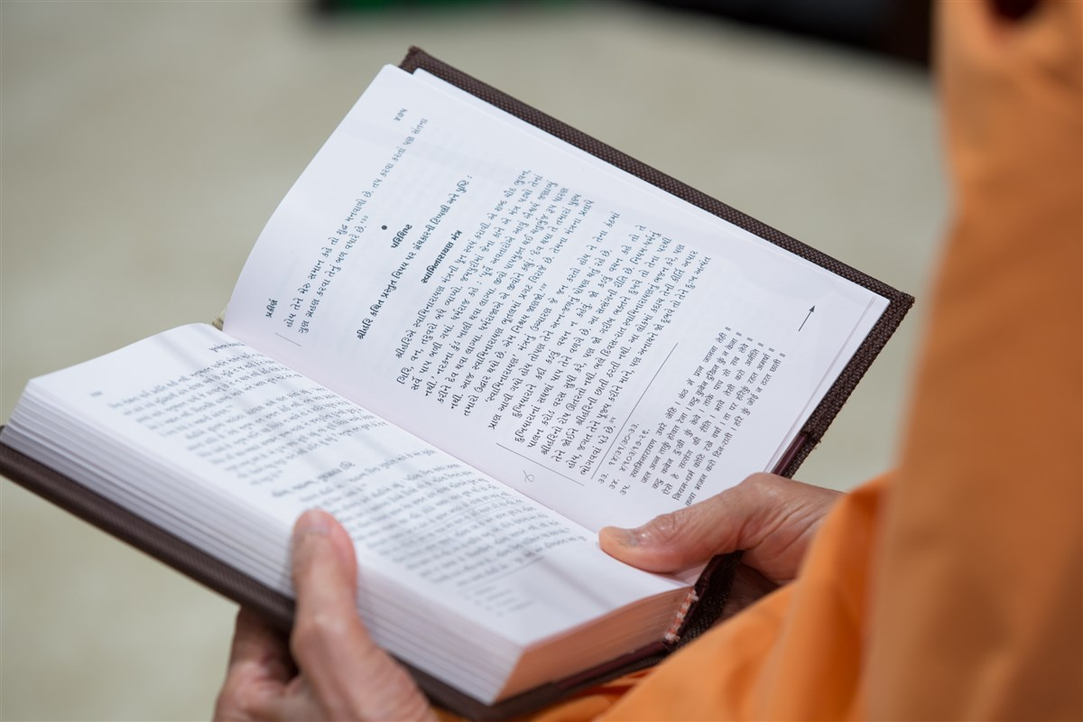Swamishri reads from 'Purushottam Bolya Prite' during the assembly
