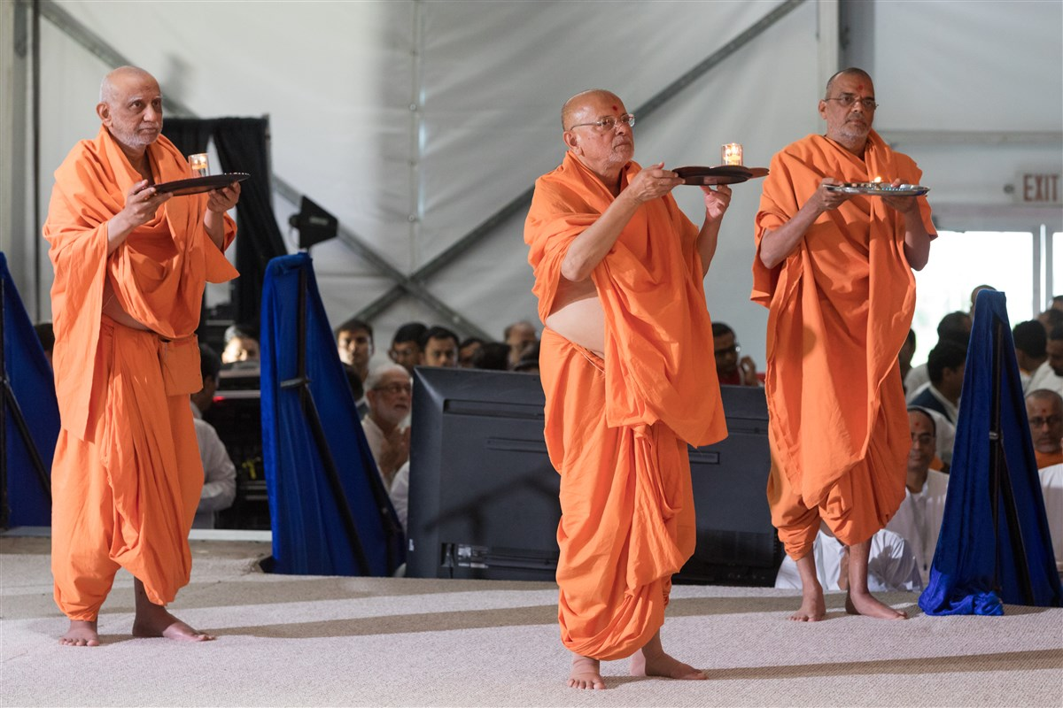 Pujya Atmaswaroopdas Swami, Pujya Ishwarcharandas Swami, and Pujya Narayanmunidas Swami perform the evening arti