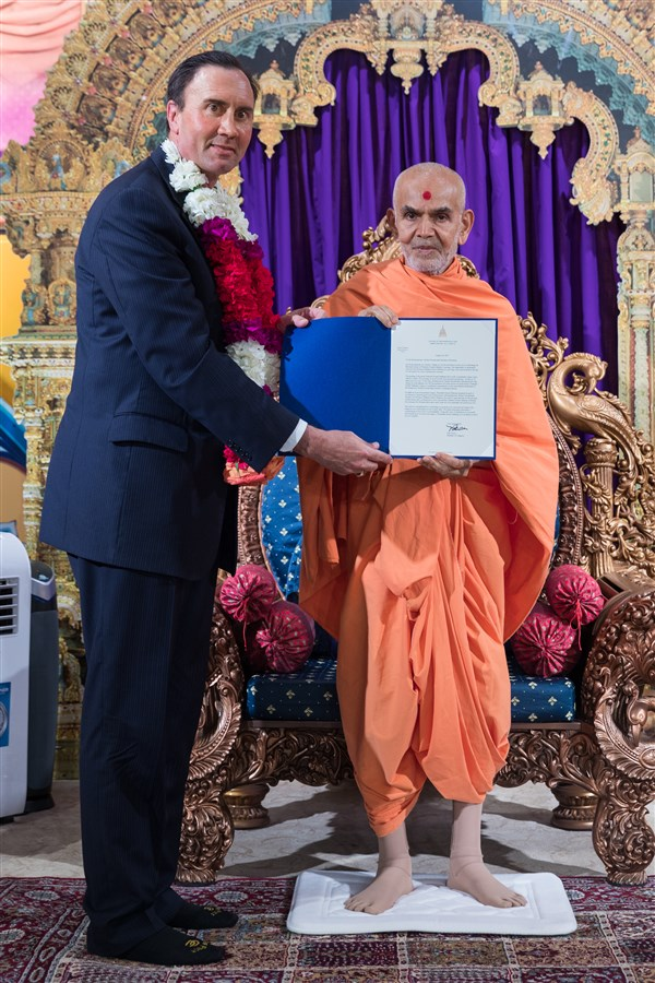 Congressman Pete Olson presents Swamishri with a letter welcoming his to the State of Texas