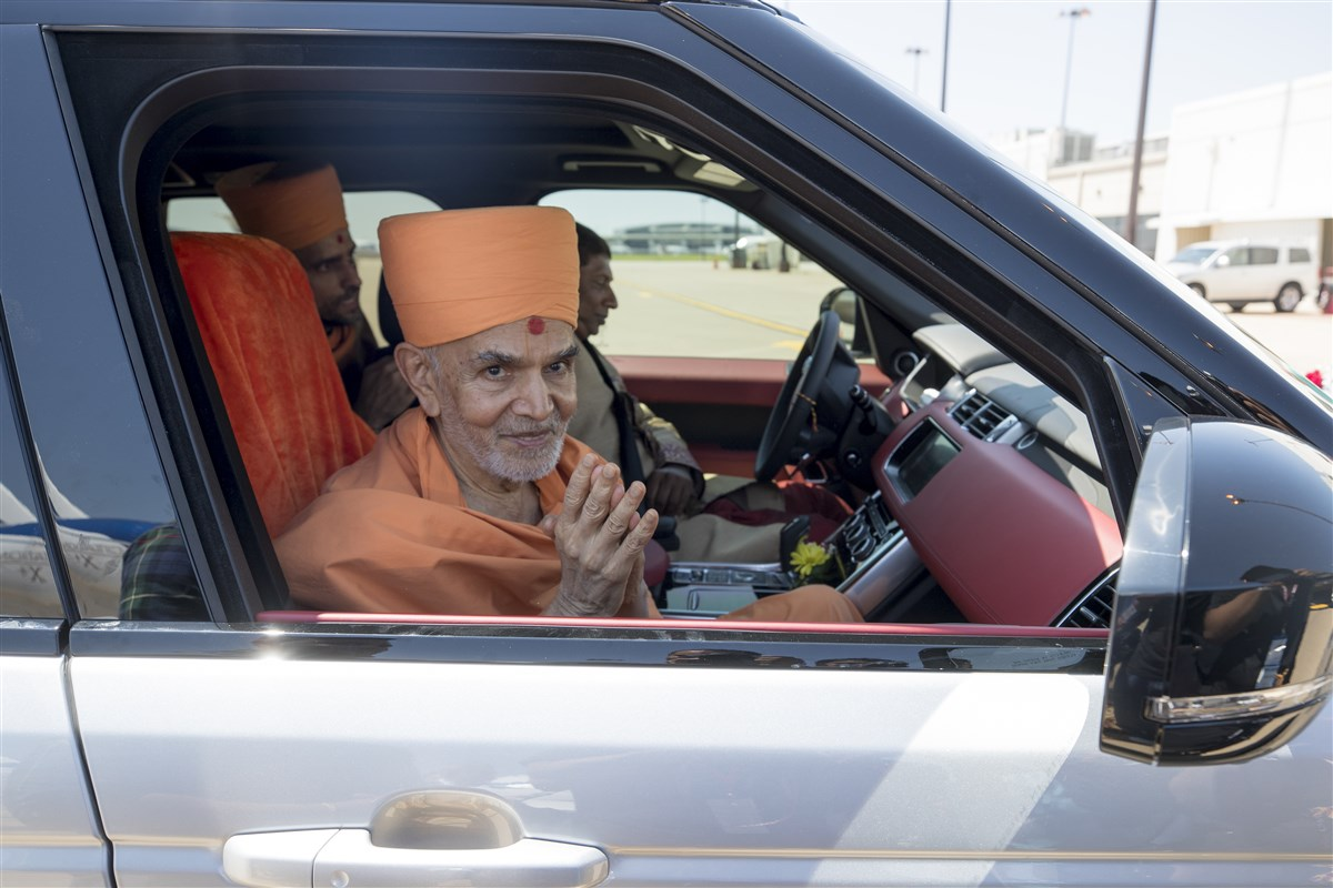 Param Pujya Mahant Swami Maharaj greets devotees with folded hands as he arrives
