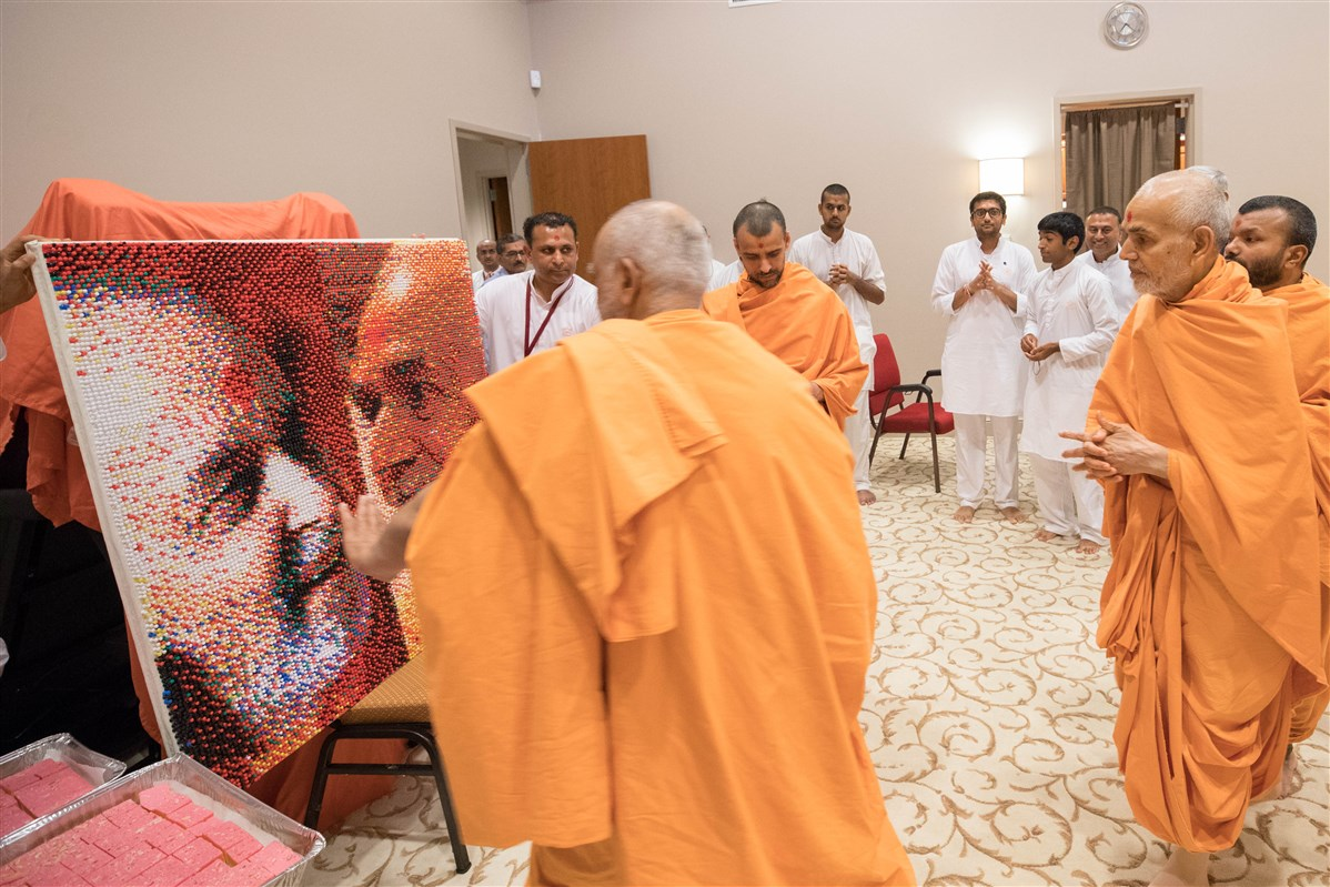 Swamishri views a bulletin board made of 18,000 thumb tacks depicting him and Brahmaswarup Pramukh Swami Maharaj, 23 August 2017