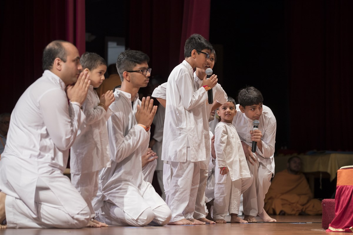 Children recite shlokas before Swamishri during his morning puja