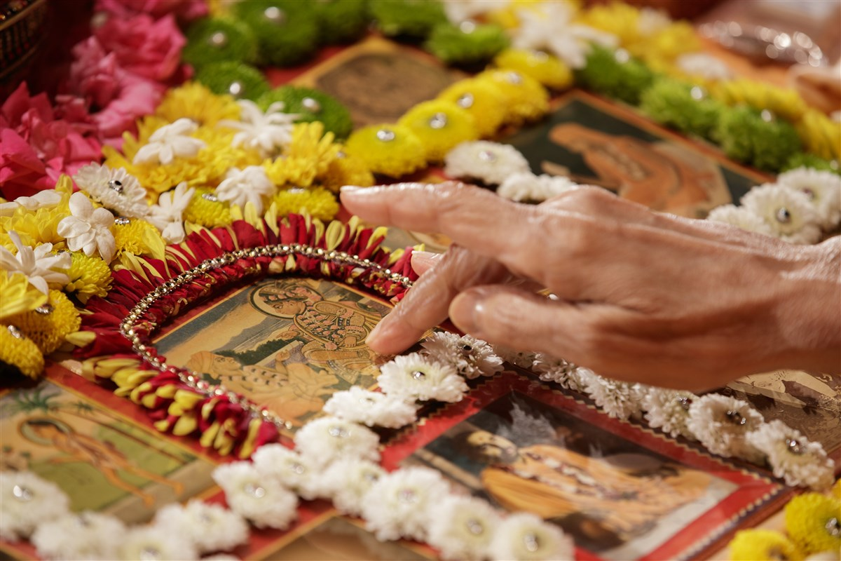 Swamishri touches the feet of the murtis in his puja