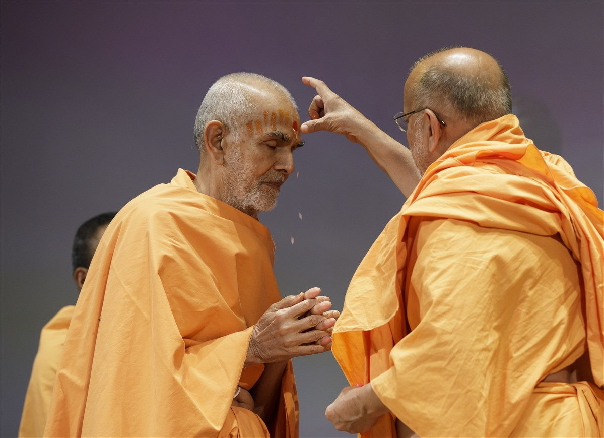 Pujya Ishwarcharan Swami applies chandlo on the forehead of Swamishri