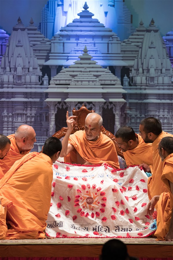 Swamishri is offered a shawl by Swamis