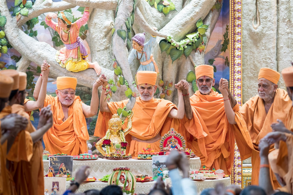Swamishri and swamis joins hands in a gesture of unity