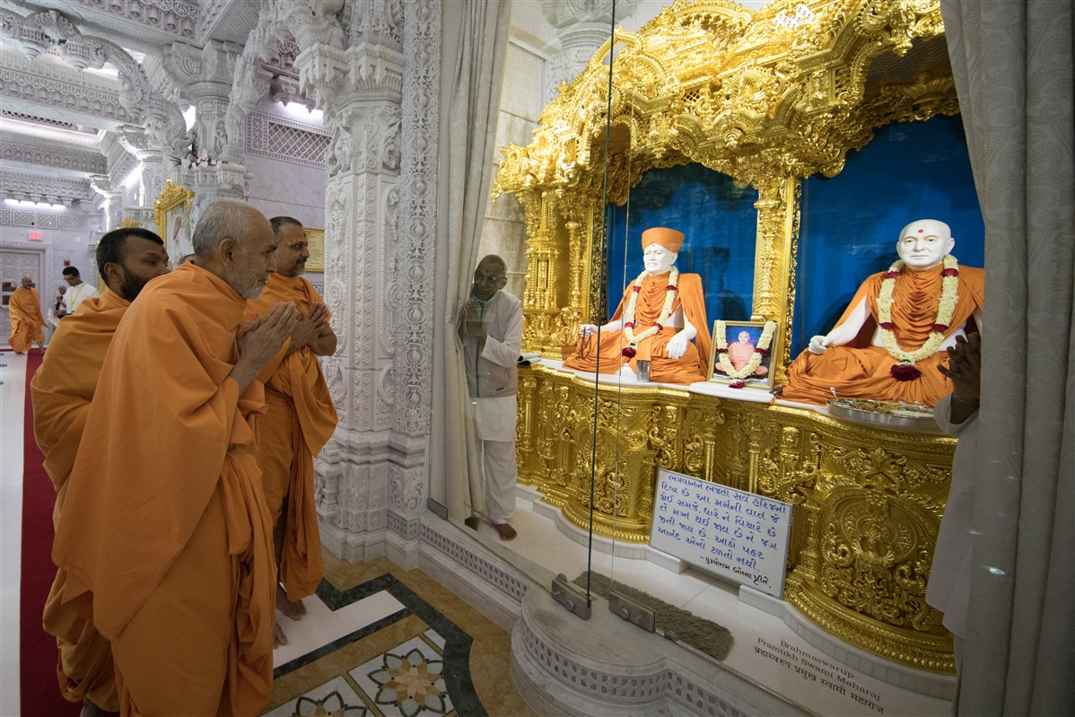 Swamishri engrossed in the darshan of Brahmaswarup Shastriji Maharaj and Brahmaswarup Pramukh Swami Maharaj