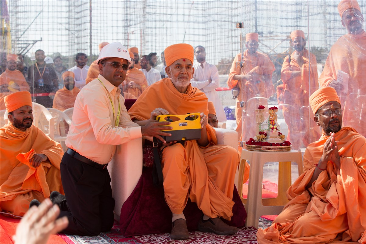 Swamishri operates the crane to install the first pillar of Swaminarayan Akshardham