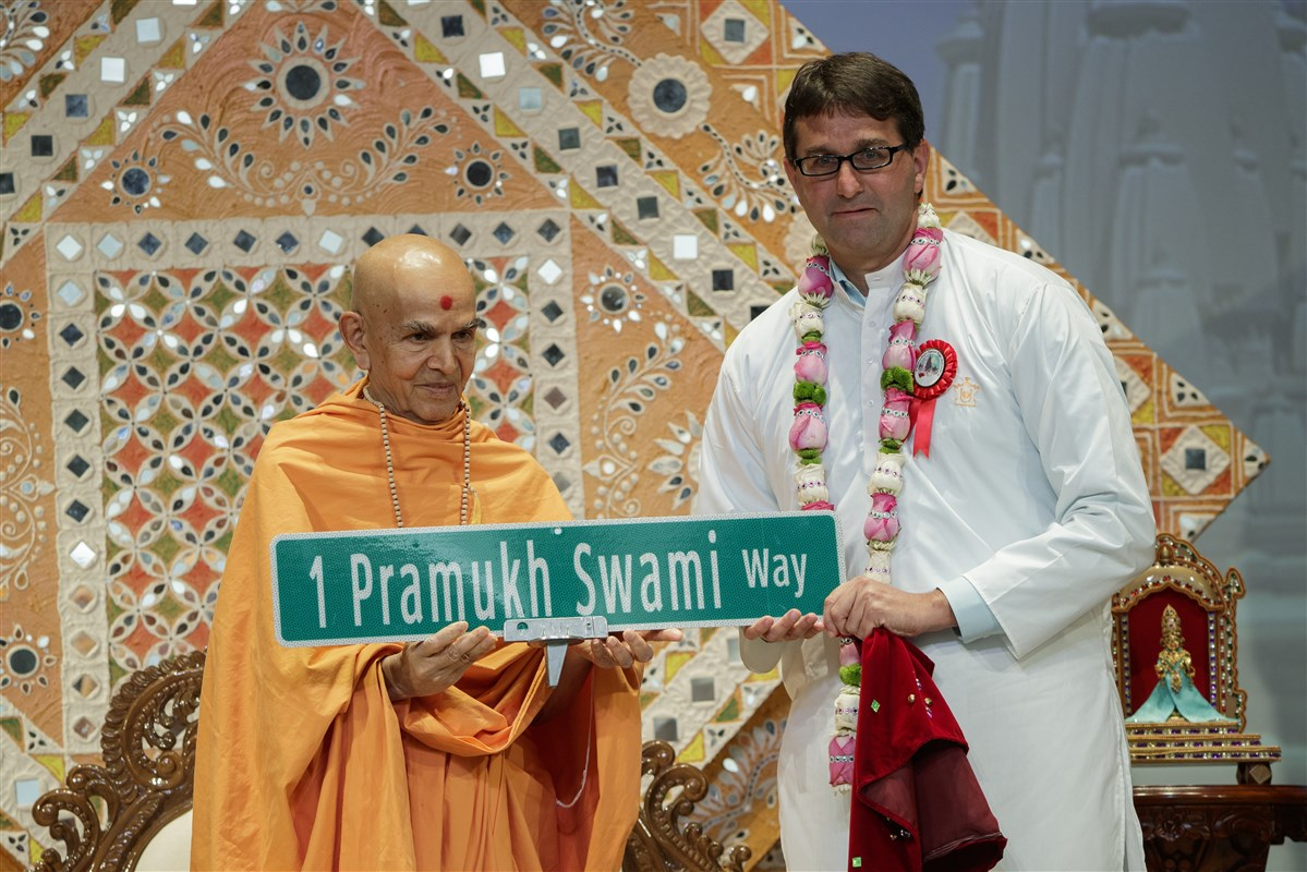 New Castle County Executive Matthew Meyer presents the new street sign to Swamishri