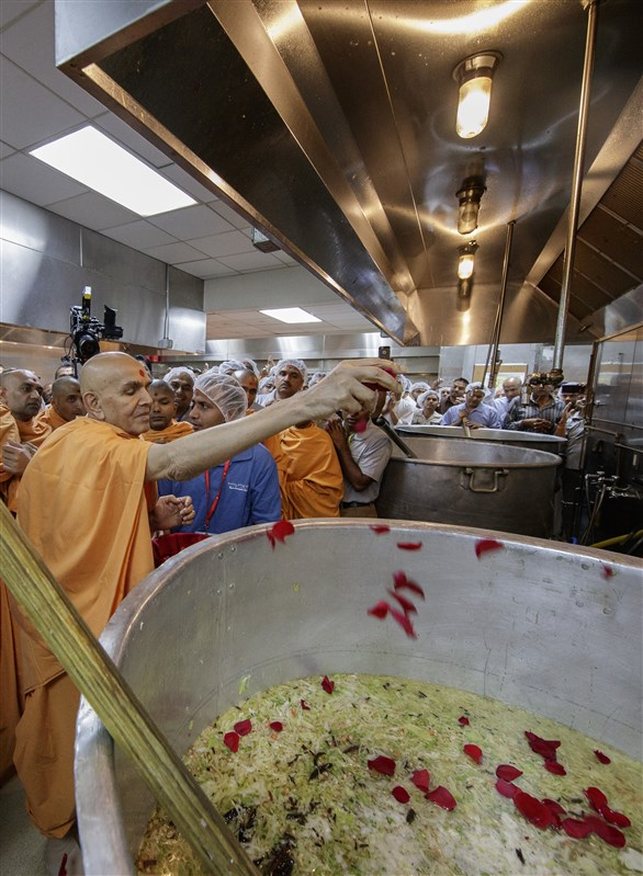 Swamishri sanctifies khichdi which was served to the devotees during HH Pramukh Swami Maharaj's Asthipushpa Visarjan later in the evening