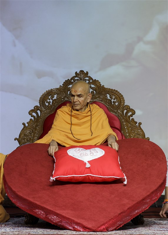 Youths present Swamishri with a pillow with 'youths are my heart' written on it