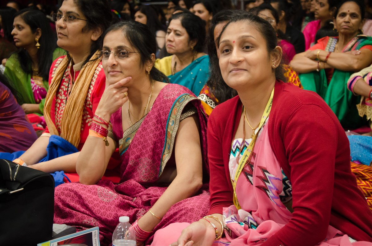 Audience members contemplating a video uniting three generations of women through Satsang and Samjan
