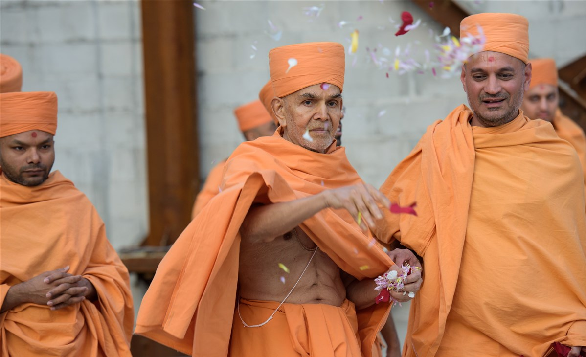 Swamishri showers flowers on the construction site